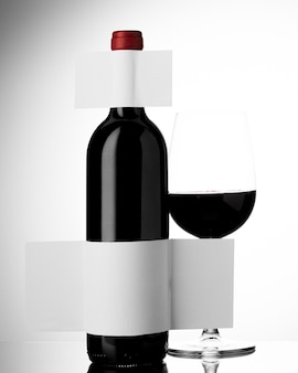 Vista frontal da garrafa de vinho com vidro e rótulo em branco