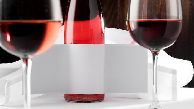 Vista frontal da garrafa de vinho transparente com rótulo em branco e copos