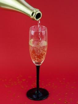 Vista frontal da garrafa derramando champanhe no copo