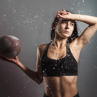 Vista frontal da jogadora de rúgbi molhada segurando uma bola