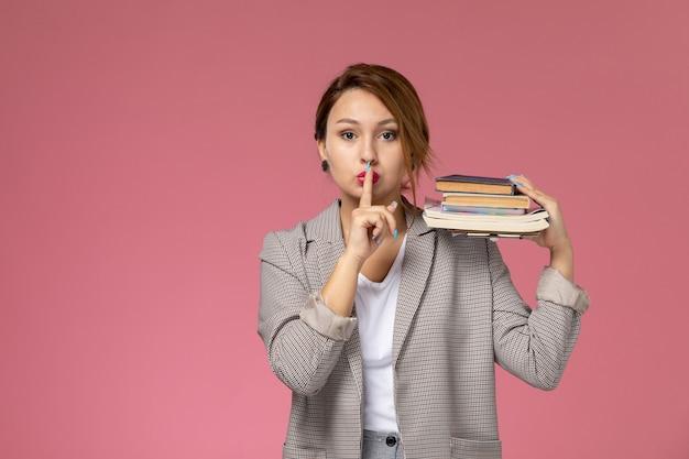Vista frontal da jovem aluna com casaco cinza e cadernos mostrando sinal de silêncio no fundo rosa aulas universidade estudo universitário