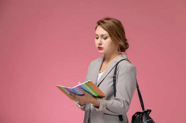 Vista frontal da jovem aluna com casaco cinza posando e escrevendo notas sobre o fundo rosa, aulas, faculdade, estudo