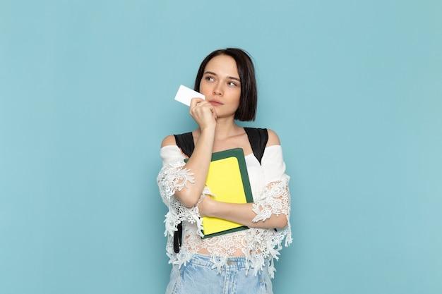 Vista frontal da jovem aluna de camisa branca jeans azul e bolsa preta segurando cadernos e cartão na escola universitária de estudante feminino espaço azul
