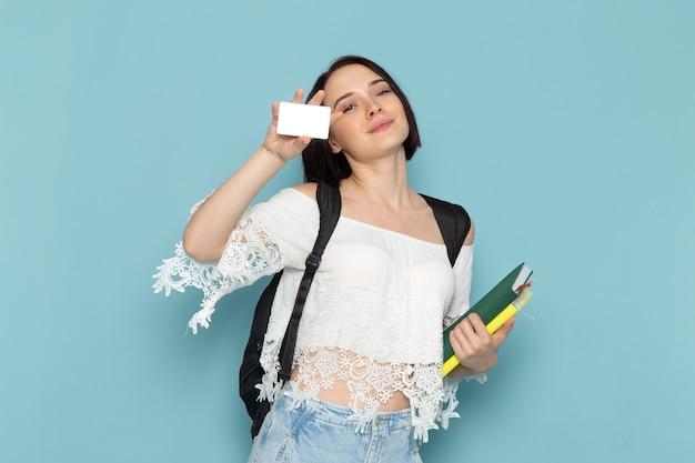 Vista frontal da jovem aluna de camisa branca jeans e bolsa preta segurando cadernos e cartão no espaço azul.