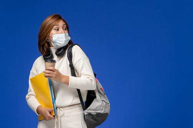 Vista frontal da jovem aluna de camisa branca usando máscara e mochila segurando arquivos e café na mesa azul.