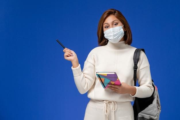 Vista frontal da jovem aluna em camisa branca usando máscara com bolsa e caderno com caneta na parede azul