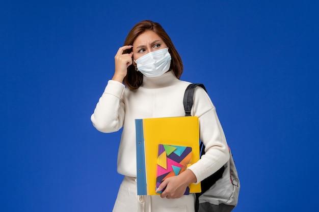 Vista frontal da jovem aluna em camisa branca usando máscara com bolsa e cadernos pensando na parede azul