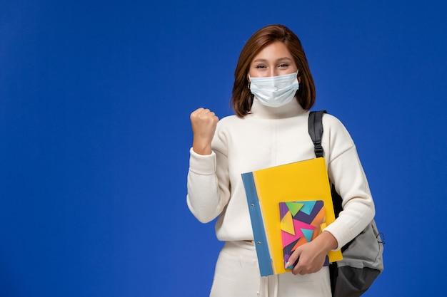 Vista frontal da jovem aluna em camisa branca usando máscara com bolsa e cadernos regozijando-se na parede azul