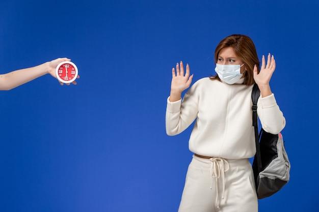 Vista frontal da jovem aluna em camisa branca usando máscara com medo de mulher e relógio na parede azul