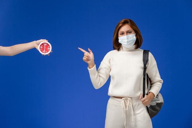 Vista frontal da jovem aluna em camisa branca usando máscara e bolsa apontando para o relógio na parede azul