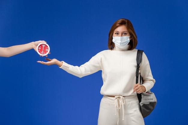 Vista frontal da jovem aluna em camisa branca, usando máscara e bolsa na parede azul