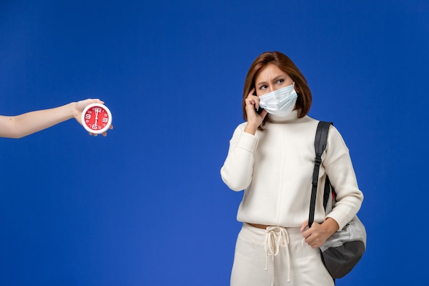 Vista frontal da jovem aluna em camisa branca usando máscara e bolsa pensando na parede azul