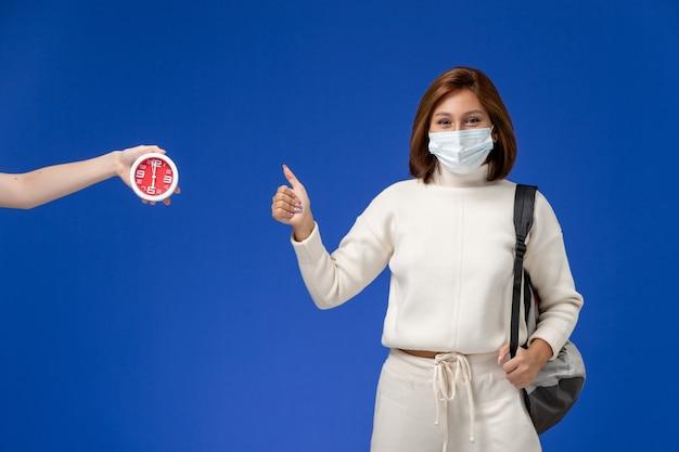 Vista frontal da jovem aluna em camisa branca, usando máscara e bolsa, posando na parede azul