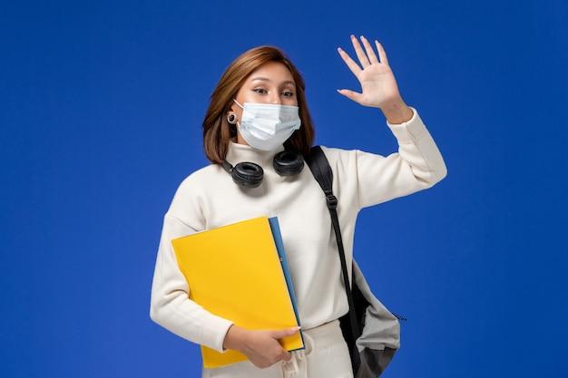Vista frontal da jovem aluna em camisa branca usando máscara e mochila segurando arquivos e acenando na parede azul