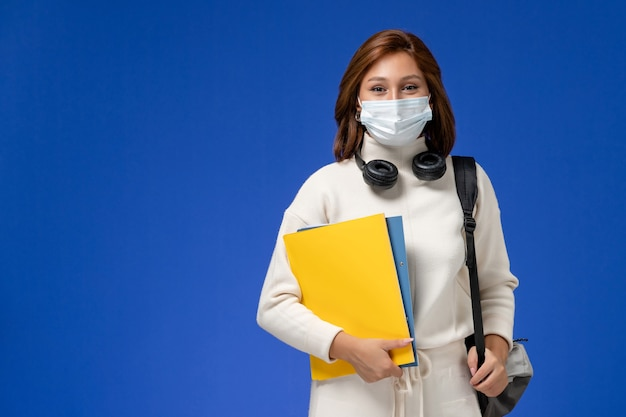 Vista frontal da jovem aluna em camisa branca, usando máscara e mochila segurando arquivos na parede azul