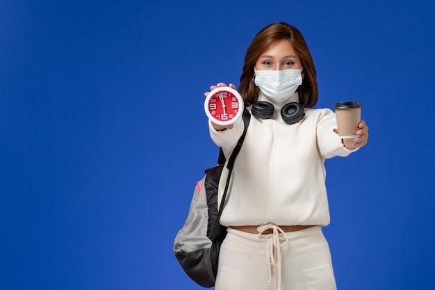 Vista frontal da jovem aluna em camisa branca usando máscara e mochila segurando café e relógio na parede azul