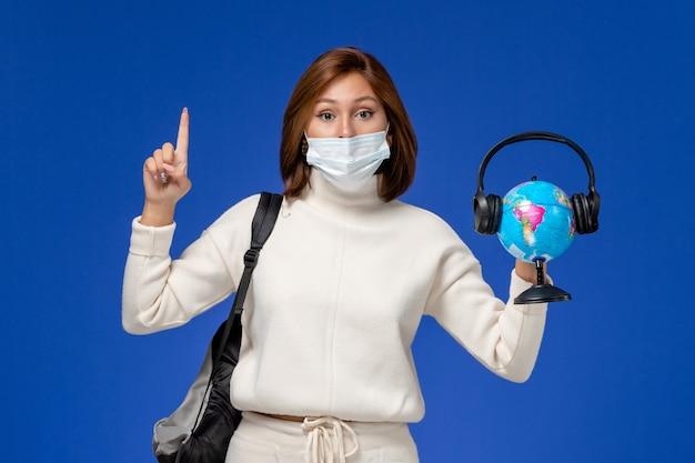 Vista frontal da jovem aluna em camisa branca usando máscara e mochila segurando o globo com fones de ouvido na parede azul