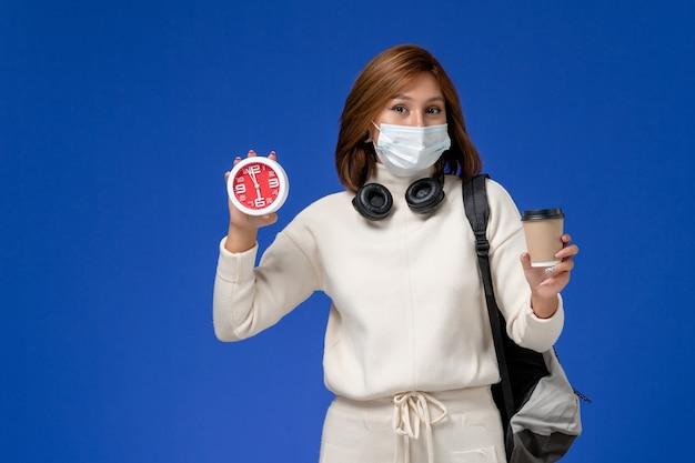 Vista frontal da jovem aluna em camisa branca usando máscara e mochila segurando o relógio e o café na parede azul