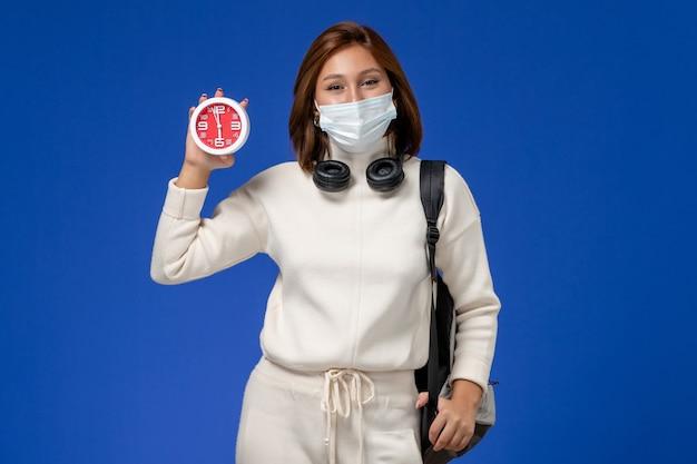 Vista frontal da jovem aluna em camisa branca usando máscara e mochila segurando o relógio na parede azul