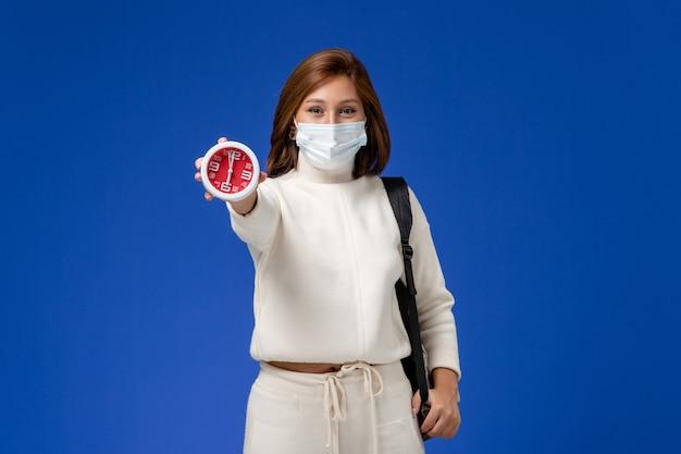 Vista frontal da jovem aluna em camisa branca, usando máscara e segurando o relógio na parede azul