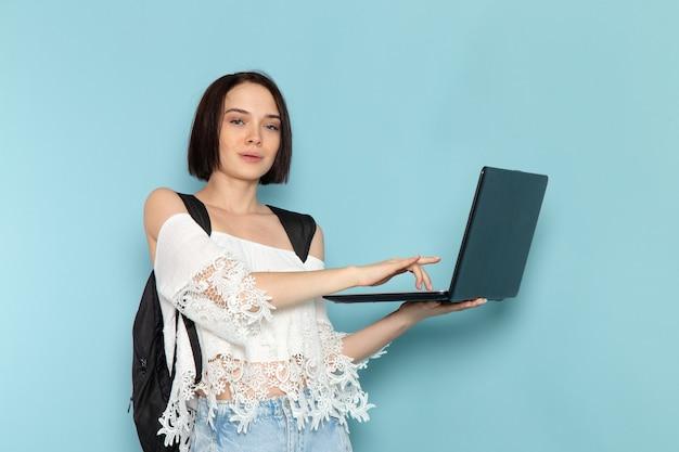 Vista frontal da jovem aluna em jeans azul de camisa branca e bolsa preta usando laptop preto na escola universitária de estudante feminino espaço azul
