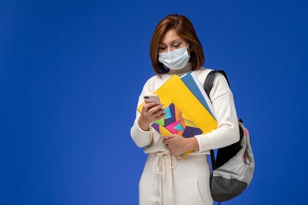 Vista frontal da jovem aluna em jérsei branco usando máscara com bolsa e cadernos e usando o telefone na parede azul