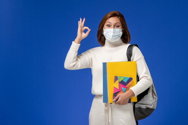 Vista frontal da jovem aluna em jérsei branco usando máscara com bolsa e cadernos na parede azul