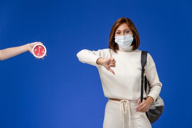 Vista frontal da jovem aluna em jérsei branco usando máscara e bolsa mostrando uma placa diferente na parede azul