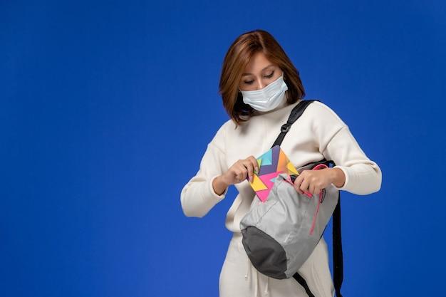 Vista frontal da jovem aluna em jérsei branco usando máscara e bolsa segurando o caderno na parede azul