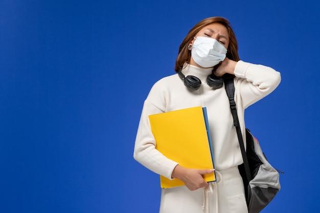 Vista frontal da jovem aluna em jérsei branco usando máscara e mochila segurando arquivos com dor de pescoço na parede azul