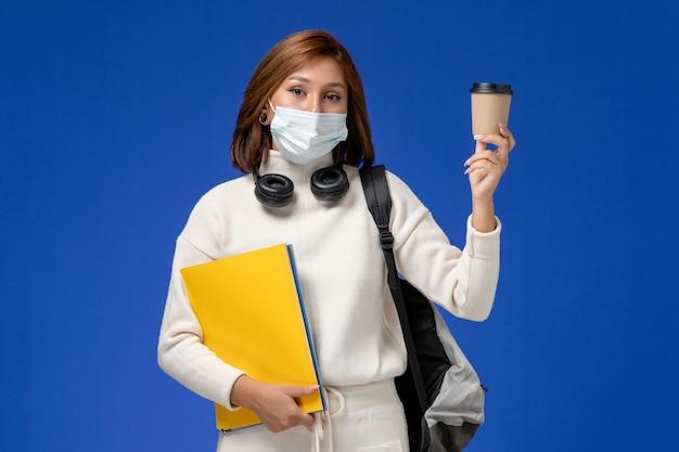 Vista frontal da jovem aluna em jérsei branco usando máscara e mochila segurando arquivos e café na parede azul