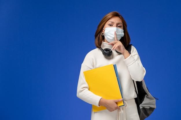 Vista frontal da jovem aluna em jérsei branco usando máscara e mochila segurando arquivos na mesa azul.