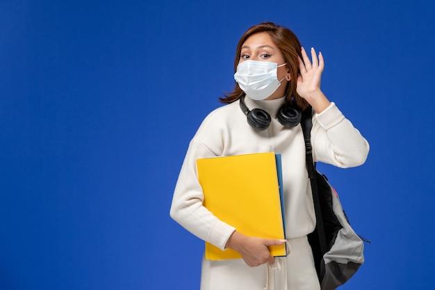 Vista frontal da jovem aluna em jérsei branco usando máscara e mochila segurando arquivos tentando ouvir na parede azul