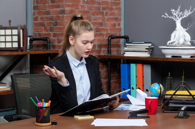 Vista frontal da jovem assistente confiante sentada em sua mesa e verificando o documento no escritório