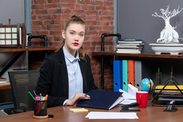 Vista frontal da jovem assistente confiante sentada em sua mesa no escritório