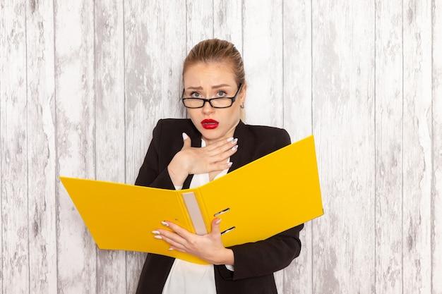 Vista frontal da jovem empresária em roupas estritas, jaqueta preta segurando arquivos e documentos na mesa branca.