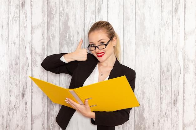 Vista frontal da jovem empresária em roupas estritas, jaqueta preta segurando arquivos e documentos na superfície branca