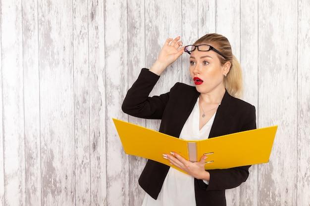 Vista frontal da jovem empresária em roupas estritas, jaqueta preta segurando arquivos e documentos verificando em superfície branca.