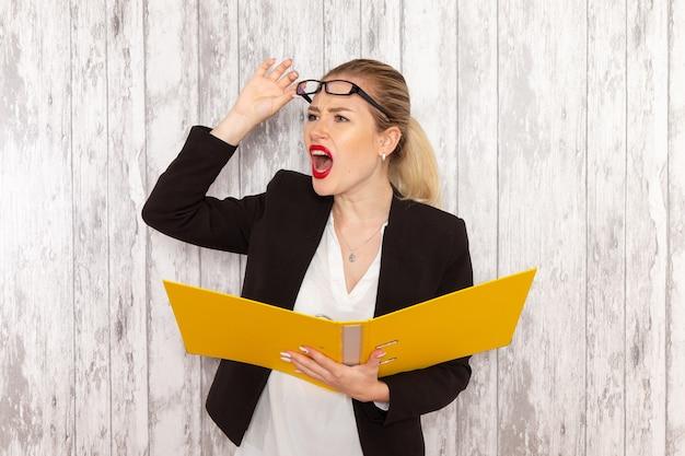 Vista frontal da jovem empresária em roupas estritas, jaqueta preta segurando arquivos e documentos verificando-os em uma superfície branca