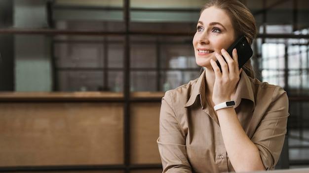 Vista frontal da jovem empresária falando ao telefone durante uma reunião