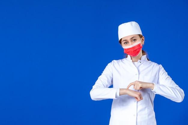 Vista frontal da jovem enfermeira em traje médico com máscara vermelha em azul