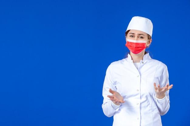 Vista frontal da jovem enfermeira estressada em traje médico com máscara vermelha no azul