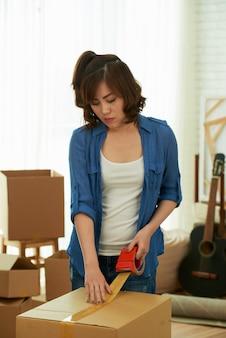 Vista frontal da jovem garota embalando a caixa com fita adesiva