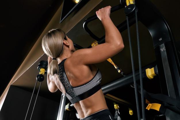 Vista frontal da jovem loira confiante, fazendo exercícios de levantamento de peso atraente jovem levantando halteres, olhando para a frente a forma do corpo treinado forte forma as pernas no peito.