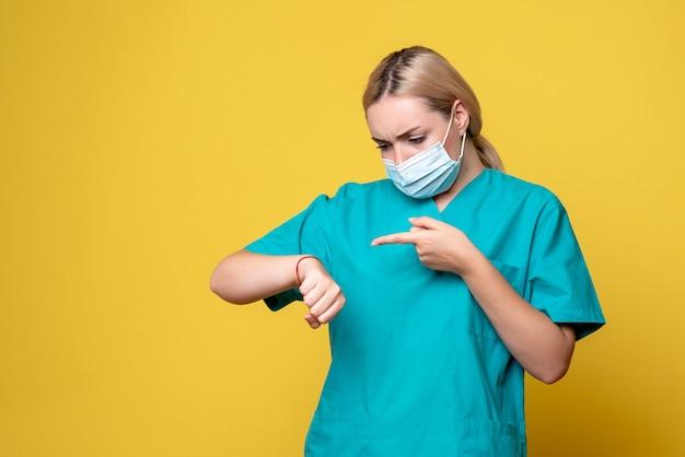 Vista frontal da jovem médica com camisa médica e máscara estéril lookign no pulso na parede amarela