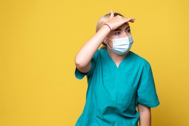 Vista frontal da jovem médica com camisa médica e máscara estéril na parede amarela