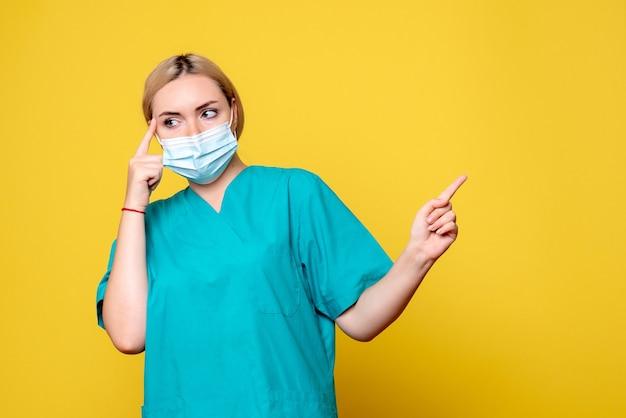 Vista frontal da jovem médica com camisa médica e máscara na parede amarela