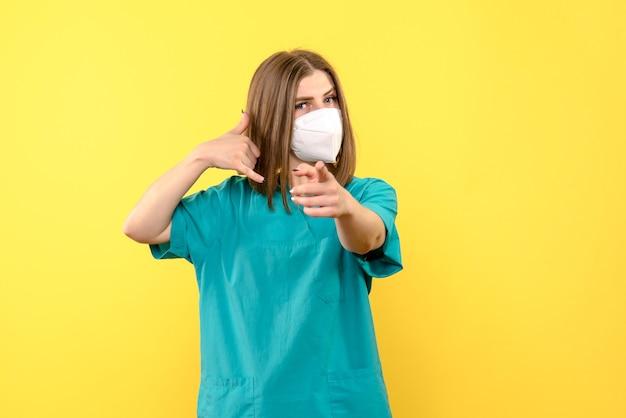 Vista frontal da jovem médica com máscara na parede amarela