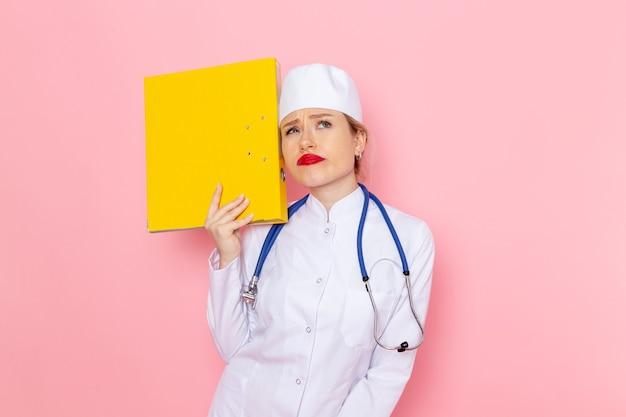 Vista frontal da jovem médica de terno branco com estetoscópio azul segurando arquivos amarelos no trabalho da garota do espaço rosa