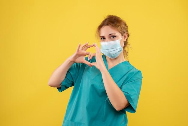 Vista frontal da jovem médica em traje médico e máscara estéril, mostrando sinal de amor na parede amarela